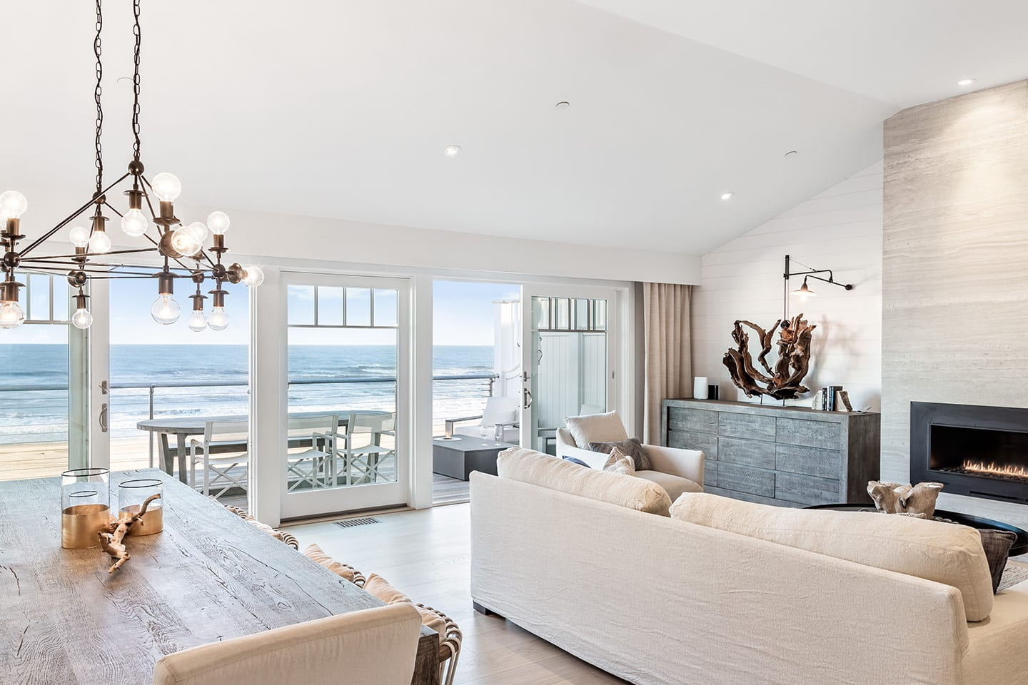 Salt Sea 5 Living room with a fireplace and dining room with a deck overlooking the ocean