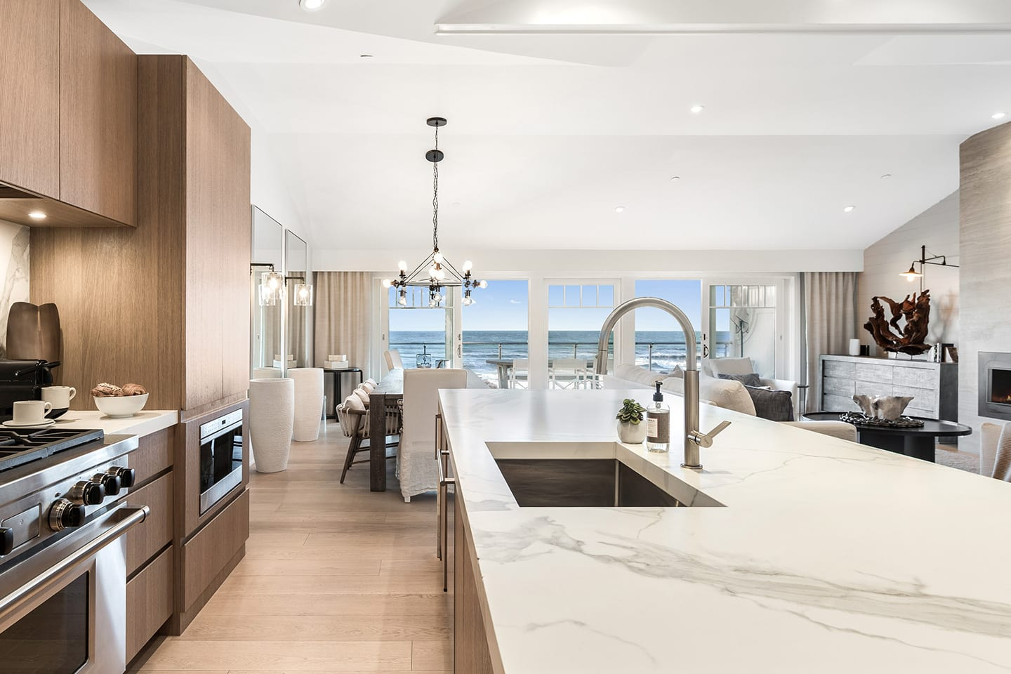 Wide view of Salt Sea 5 kitchen looking out to the living room and dining area with a deck overlooking the ocean