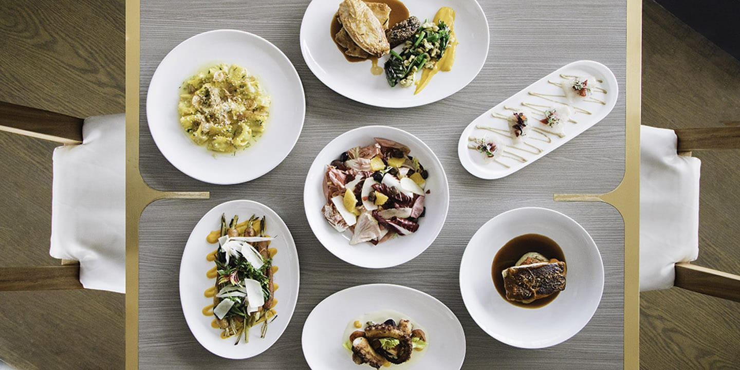 An aerial view of seven dishes at the restaurant Scarpetta.