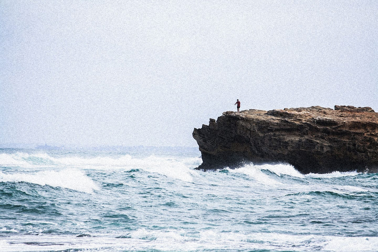 A man on a boulder fishing in the ocean.